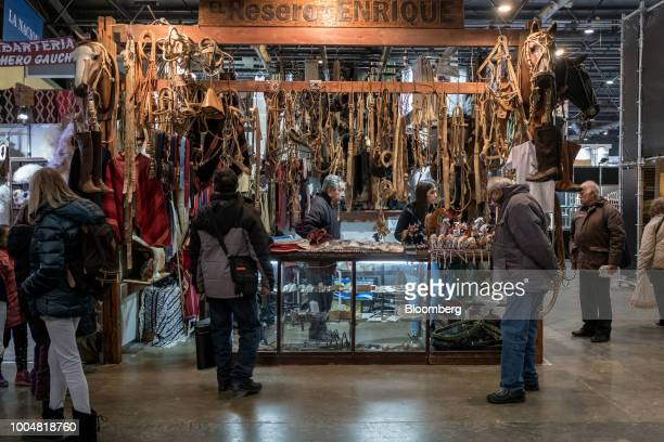 Attendees browse leather goods at the exhibition pavilion during La Exposicion Rural agricultural and livestock show in the Palermo neighborhood of...