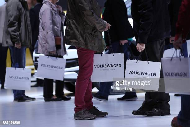 Attendees carry gift bags during Volkswagen AG's annual shareholders' meeting in Hannover Germany on Wednesday May 10 2017 Volkswagen pledged to...