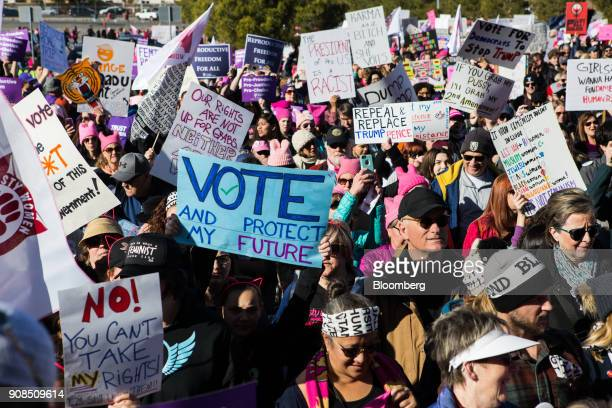 Attendees carry signs and wave flags before entering the Sam Boyd Stadium during the Women's March OneYear Anniversary Power To The Polls event in...