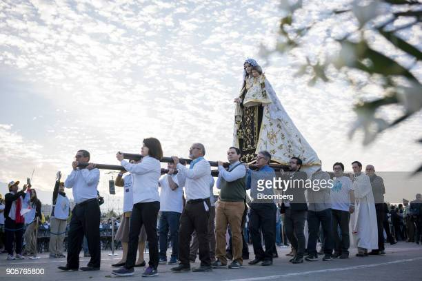 Attendees carry the statue of Virgin Carmen as Pope Francis not pictured arrives to give mass at O'Higgins Park in Santiago Chile on Tuesday Jan 16...