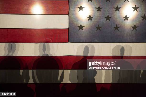 attendees cast shadows on a large u.s. flag during a town hall event - stimmabgabe stock-fotos und bilder