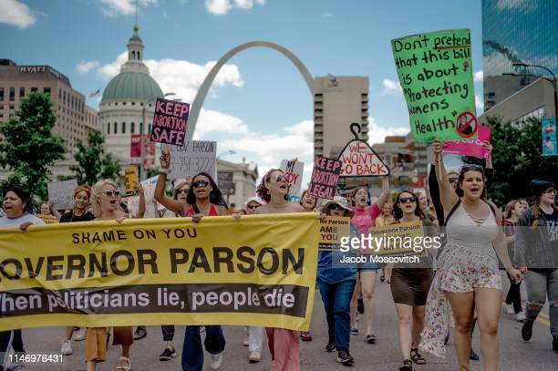 Attendees chant and march through downtown St. Louis during a rally and march to protest the closure of the last abortion clinic in Missouri on May...