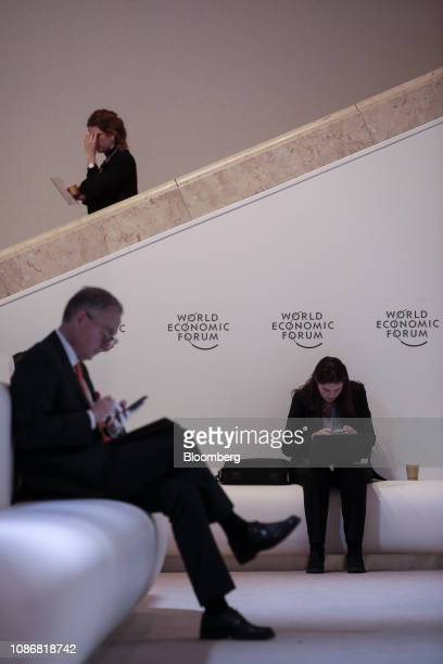 Attendees check their devices between sessions on day two of the World Economic Forum in Davos Switzerland on Wednesday Jan 23 2019 World leaders...