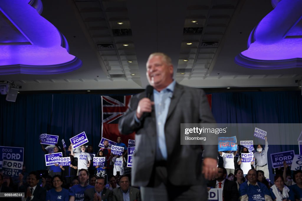 Attendees cheer and hold placards as Doug Ford, Progressive Conservative Party candidate for Ontario Premier, foreground, speaks during a campaign rally in Mississauga, Ontario, Canada, on Wednesday, May 16, 2018. Ford, who's campaigning to 'take back' Ontario with an agenda to shrink government and reduce spending, is the brother of the late scandal-plagued Toronto mayor Rob Ford. Photographer: Cole Burston/Bloomberg via Getty Images