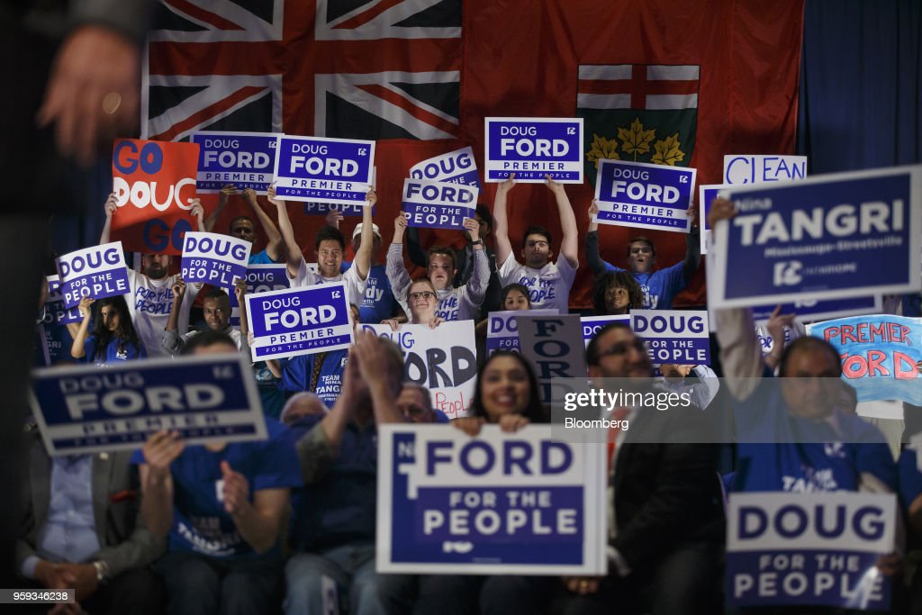 Attendees cheer and hold placards during a campaign rally for Doug Ford, Progressive Conservative Party candidate for Ontario Premier, not pictured, in Mississauga, Ontario, Canada, on Wednesday, May 16, 2018. Ford, who's campaigning to 'take back' Ontario with an agenda to shrink government and reduce spending, is the brother of the late scandal-plagued Toronto mayor Rob Ford. Photographer: Cole Burston/Bloomberg via Getty Images