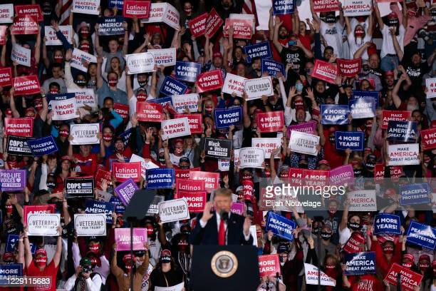Attendees cheer and hold up signs as President Donald Trump speaks at a campaign rally on October 16, 2020 in Macon, Georgia. President Trump...