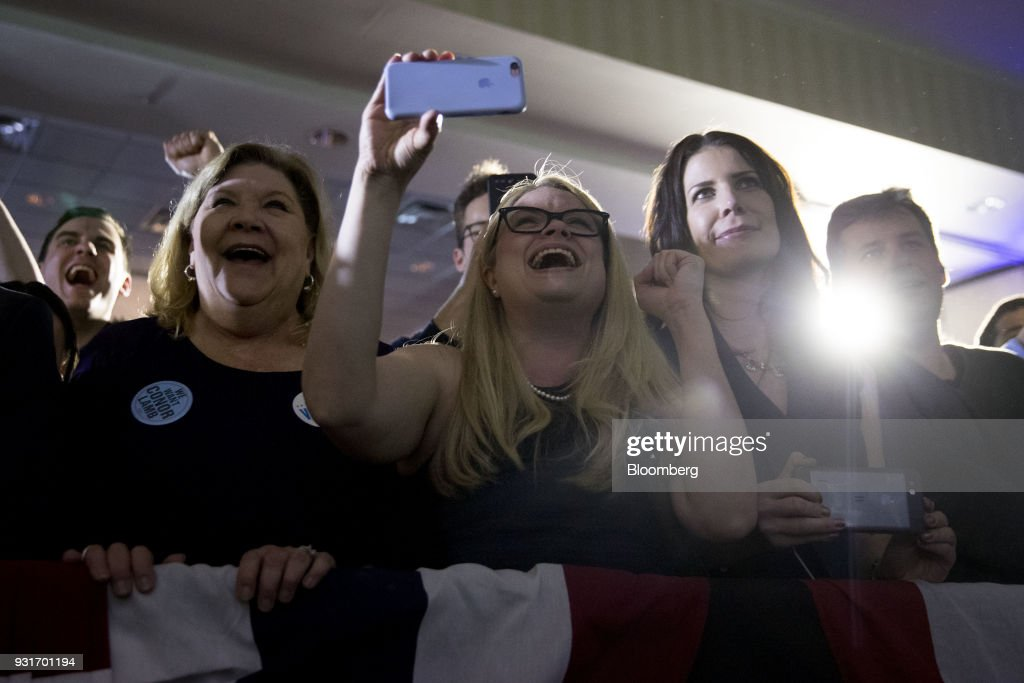 Attendees cheer as Conor Lamb, Democratic candidate for the U.S. House of Representatives, not pictured, speaks during an election night rally in Canonsburg, Pennsylvania, U.S., on Wednesday, March 14, 2018. Lamb and Republican Rick Saccone were locked in a tight contest for a House seat in Pennsylvania that may be a bellwether for the fall elections that will decide control of Congress. Photographer: Andrew Harrer/Bloomberg via Getty Images