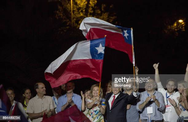 Attendees cheer as Sebastian Pinera Chile's presidentelect and wife Cecilia Morel left wave Chilean national flags at the National Renewal party...
