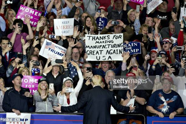 Attendees cheer as US President Donald Trump center arrives to speak at a rally in Washington Michigan US on Saturday April 28 2018 Trumptook on...