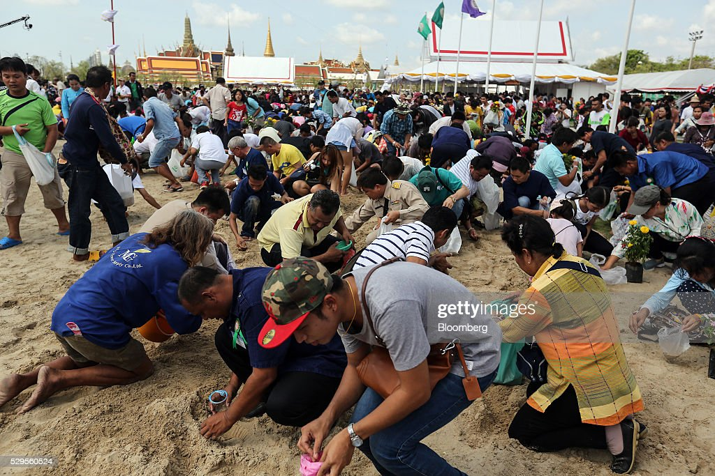 Attendees collect 'sacred' rice grains from the ground after the Royal Ploughing Ceremony at Sanam Luang park in Bangkok, Thailand, on Monday, May 9, 2016. This year may be a better one for Thai rice production. At least, that's what two sacred oxen and a ceremonial lord forecast at an annual ploughing ceremony. Photographer: Dario Pignatelli/Bloomberg via Getty Images