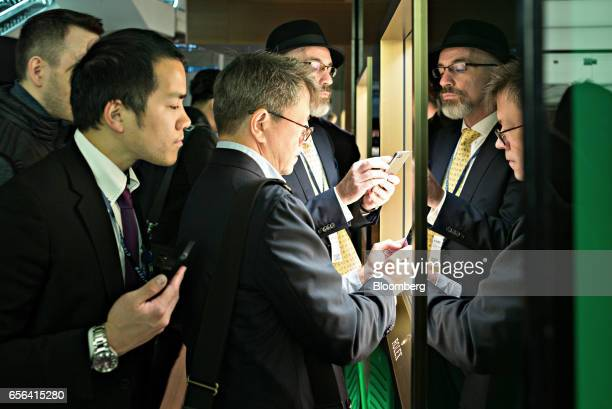 Attendees crowd around a Rolex Group display case to take photographs during the 2017 Baselworld luxury watch and jewellery fair in Basel Switzerland...