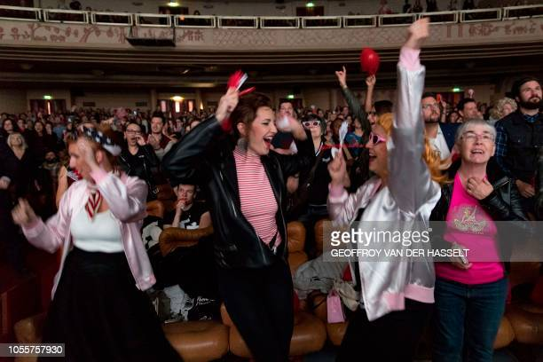 Attendees dance and sing as they watch the movie during a special anniversary karaoke party for the 40 years of the release of the US musical...