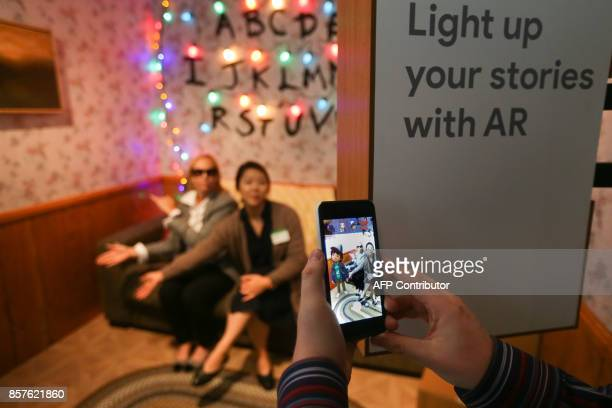 Attendees demo the augmented reality integration of the new Google Pixel 2 smartphone using the demigorgon from Netflix's Stranger Things series at a...