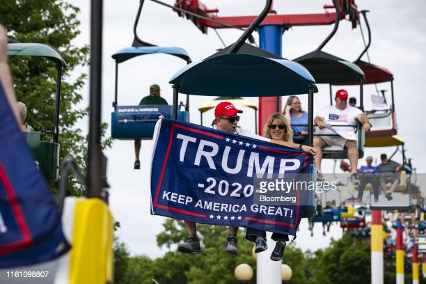 Attendees display flags supporting US President Donald Trump as they ride the Sky Glider attraction during the Iowa State Fair in Des Moines Iowa US...