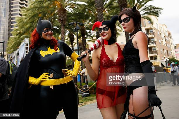 Attendees dressed as DC Comics' Batman Harley Quinn and Catwoman stand for a photograph during the ComicCon International convention in San Diego...