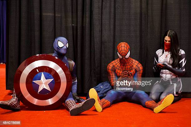 Attendees dressed as Marvel's Captain Spidey left Spiderman center and Silk take a break during the D23 Expo 2015 in Anaheim California US on Friday...