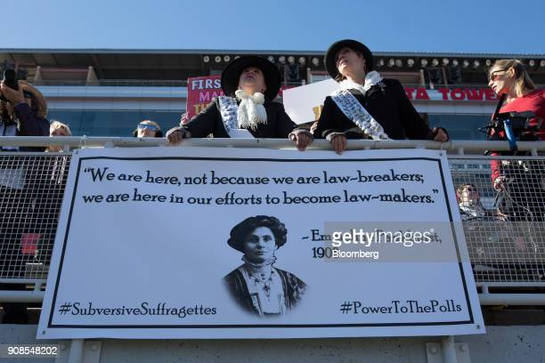 Attendees dressed in the likeness of suffragettes stand behind a banner featuring British suffragist Emmeline Pankhurst during the Women's March...