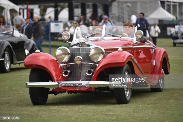 Attendees drive in a 1937 MercedesBenz AG 540K Special Roadster convertible vehicle during the 2017 Amelia Island Concours d'Elegance in Amelia...