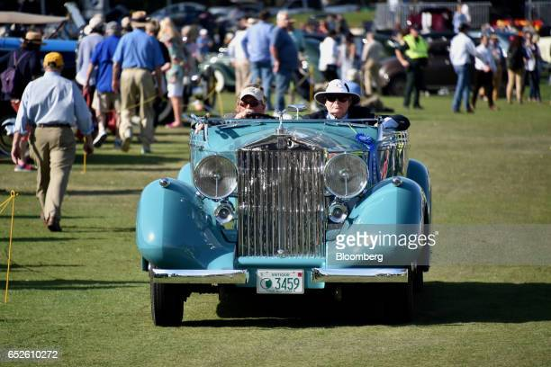 Attendees drive in a 1937 RollsRoyce Phantom III convertible luxury vehicle during the 2017 Amelia Island Concours d'Elegance in Amelia Island...