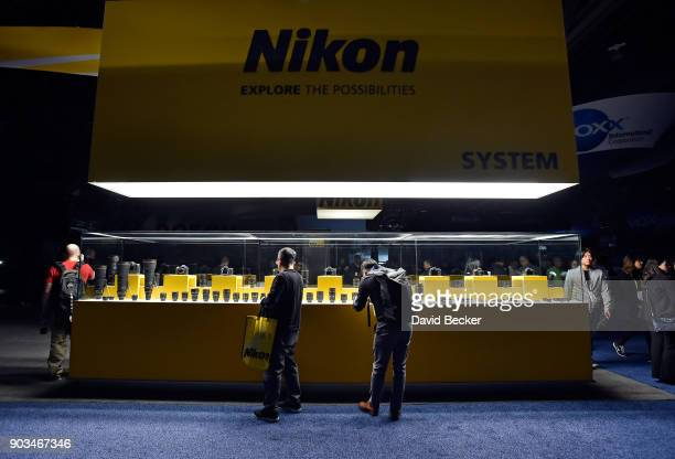 Attendees examine one of a few lighted displays at the Nikon booth after power was lost inside the central hall during CES 2018 at the Las Vegas...