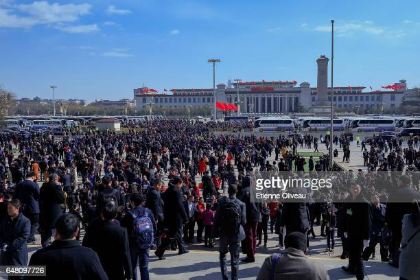 Attendees exit the Great Hall of the People toward their buses parked on Tiananmen Square after the opening session of the National People's Congress...