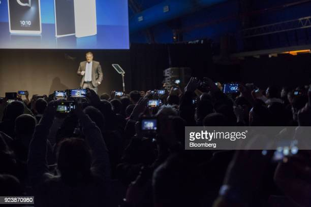 Attendees film Christian Gatti global president of Alcatel Mobile on their smartphones as he speaks on stage during an AlcatelLucent SA launch event...