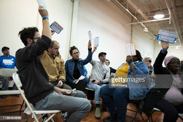 Attendees for Senator Bernie Sanders an Independent from Vermont and 2020 presidential candidate hold up their Presidential Preference Cards during...