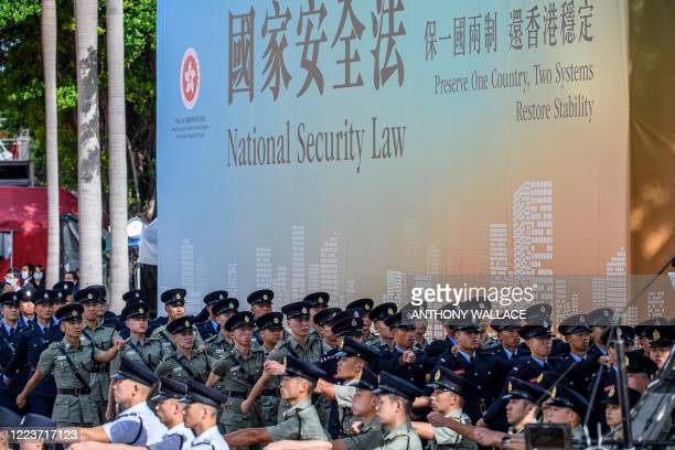 Attendees from various forces march next to a banner supporting the new national security law at the end of a flagraising ceremony to mark the 23rd...