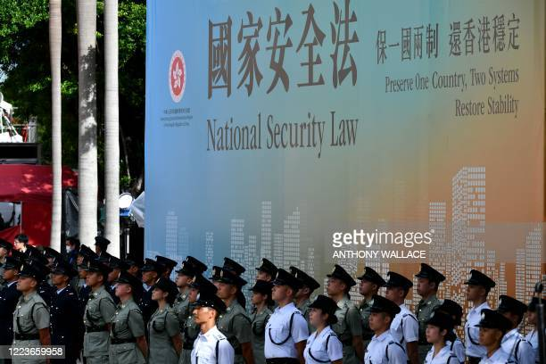 Attendees from various forces stand next to a banner supporting the new national security law during a flagraising ceremony to mark the 23rd...