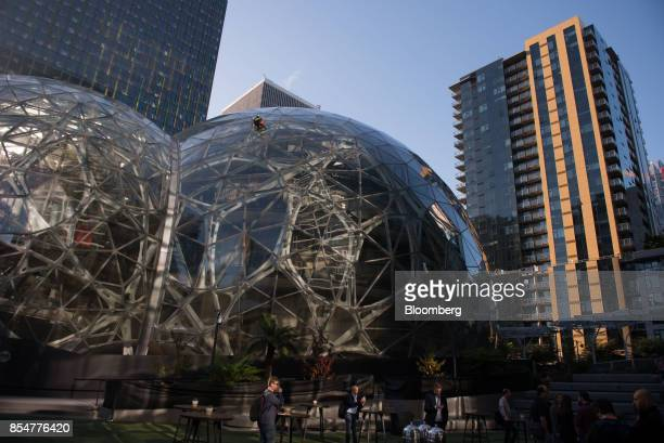 Attendees gather outside of the Amazoncom Inc Spheres ahead of the company's product reveal launch event in downtown Seattle Washington US on...