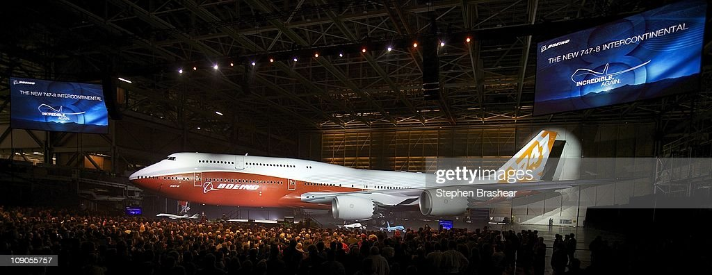 Attendees gather to view a Boeing 747-8 Intercontinental, the company's newest and largest passenger plane, during an unveiling ceremony February 13, 2011 at the company's factory in Everett, Washington. The new plane features quieter, more fuel efficient engines, more seating and a redesigned interior. The first plane also featured a red paint job, a departure from the traditional Boeing blue.