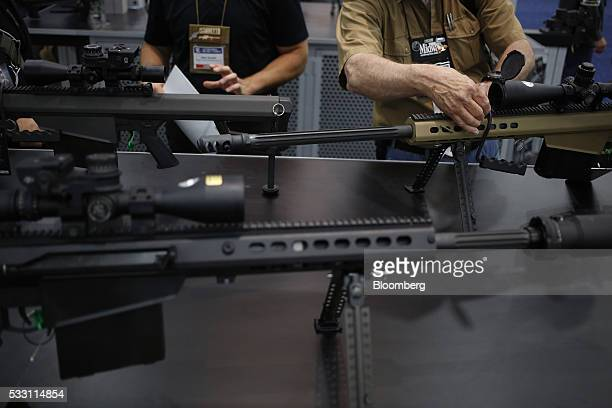 Attendees handle Barrett Firearms Manufacturing 50 caliber sniper rifles on the exhibit floor during the National Rifle Association annual meeting in...