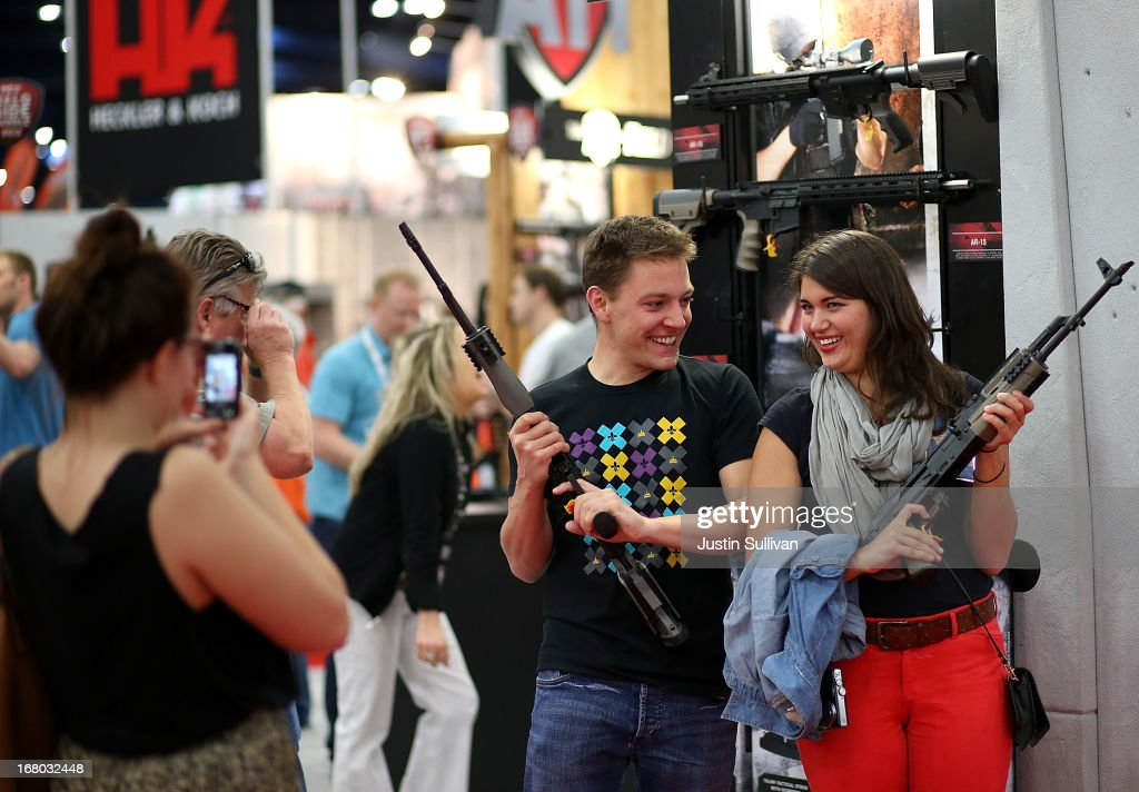Attendees hold assault rifles as they pose for a photo during the 2013 NRA Annual Meeting and Exhibits at the George R. Brown Convention Center on May 4, 2013 in Houston, Texas. More than 70,000 people are expected to attend the NRA's 3-day annual meeting that features nearly 550 exhibitors, gun trade show and a political rally. The Show runs from May 3-5.