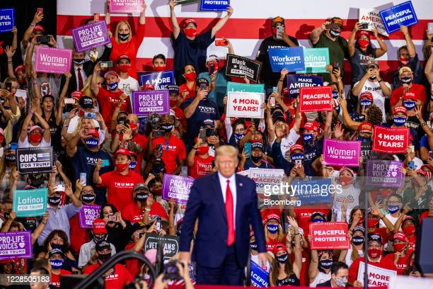 Attendees hold banners as U.S. President Donald Trump stands during a campaign rally at Xtreme Manufacturing's warehouse in Henderson, Nevada, U.S.,...