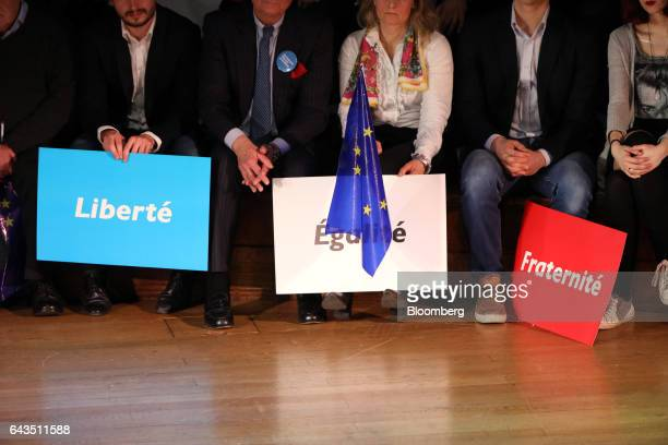 Attendees hold campaign placards stating 'Liberte Egalite Fraternite' as Emmanuel Macron French presidential candidate not pictured speaks at a...