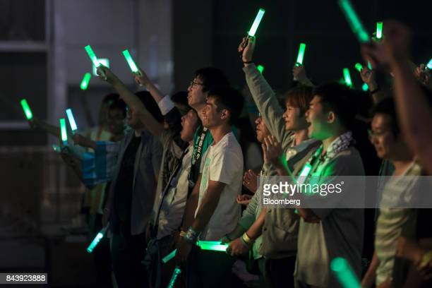 Attendees hold hand lights as they listen to musicians perform on a stage during the Hatsune Miku Magical Mirai 2017 event at the Makuhari Messe...