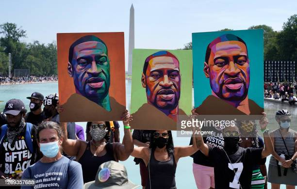 Attendees hold images of George Floyd as they participate in the March on Washington at the Lincoln Memorial August 28, 2020 in Washington, DC. Today...