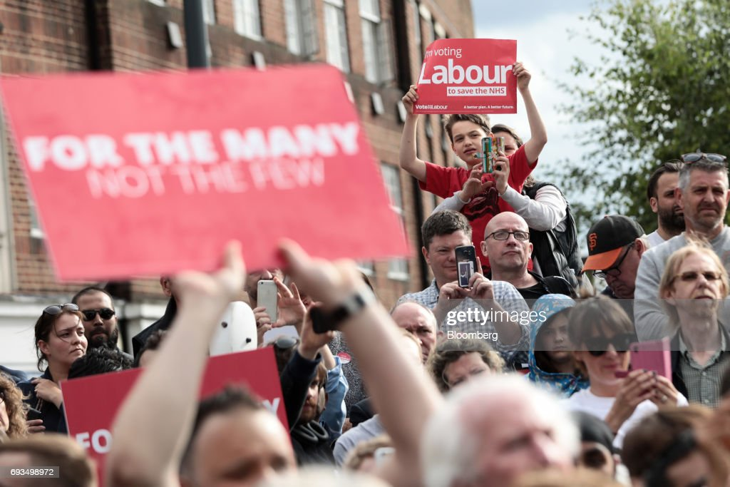 Attendees hold placards while listening to Jeremy Corbyn, leader of the U.K. opposition Labour Party, speak during a general-election campaign rally in Watford, U.K., on Wednesday, June 7, 2017. The prime minister Theresa May and Corbyn, set out on whistle-stop tours of the country ahead of Thursday's vote, with polls all showing May's Conservatives ahead but disagreeing about whether the race is close.r. Photographer: Simon Dawson/Bloomberg via Getty Images