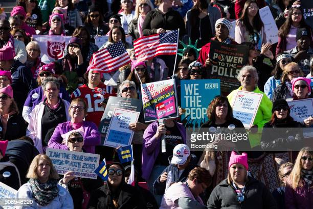 Attendees hold signs and wave American flags during the Women's March OneYear Anniversary Power To The Polls event in Las Vegas Nevada US on Sunday...