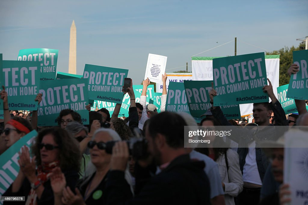 Attendees hold signs during the Moral Action on Climate Justice rally on the National Mall in Washington, D.C., U.S., on Thursday, Sept. 24, 2015. 'Climate change is a problem which can no longer be left to a future generation,' Pope Francis said at the White House yesterday. Photographer: Oliver Contreras/Bloomberg via Getty Images