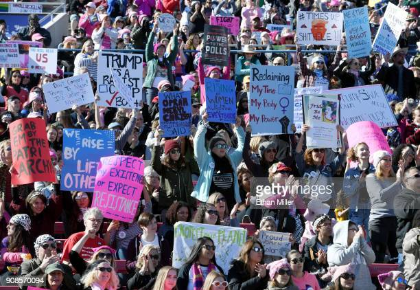 Attendees hold signs during the Women's March Power to the Polls voter registration tour launch at Sam Boyd Stadium on January 21 2018 in Las Vegas...