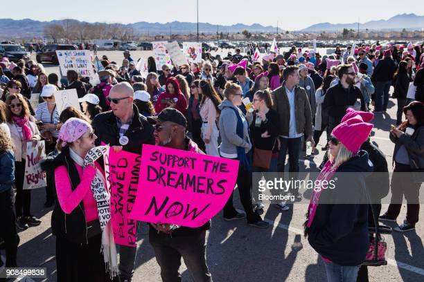 Attendees hold signs outside before entering the Sam Boyd Stadium during the Womens March OneYear Anniversary Power To The Polls event in Las Vegas...