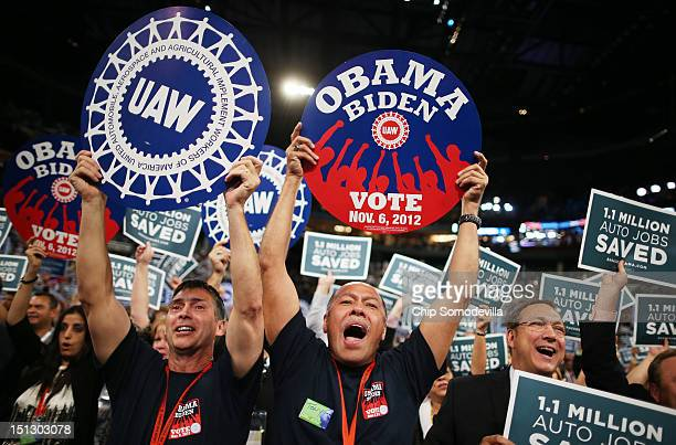 Attendees hold signs that say 11 Million Auto Jobs Saved and union related signs during day two of the Democratic National Convention at Time Warner...
