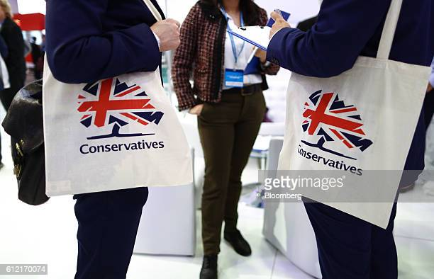 Attendees hold tote bags branded with the Conservatives Party logo during the second day of the party's annual conference in Birmingham UK on Monday...