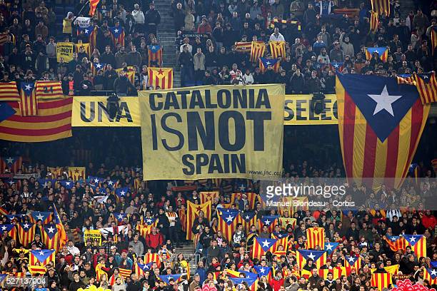 Attendees hold up a banner reading 'Catalonia Is Not Spain' and wave proindependence Catalan flags during the international friendly match between...