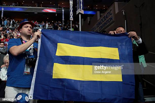 Attendees hold up a flag with the Human Rights Campaign logo during the fourth day of the Democratic National Convention at the Wells Fargo Center,...