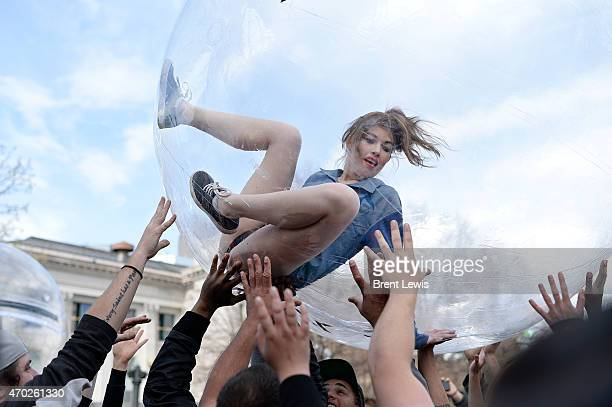 Attendees hold up a model while inside of a large inflatable ball during the Accomplice Clothing fashion show on Saturday April 18 2015 at Civic...