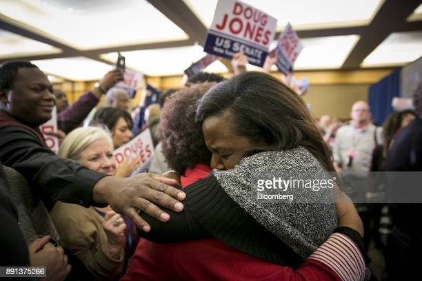 Attendees hug while celebrating during an election night party for Senatorelect Doug Jones a Democrat from Alabama in Birmingham Alabama US on...