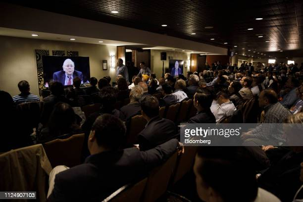 Attendees in an overflow room watch Charlie Munger vice chairman of Berkshire Hathaway Inc speak on television screens during the Daily Journal Corp...