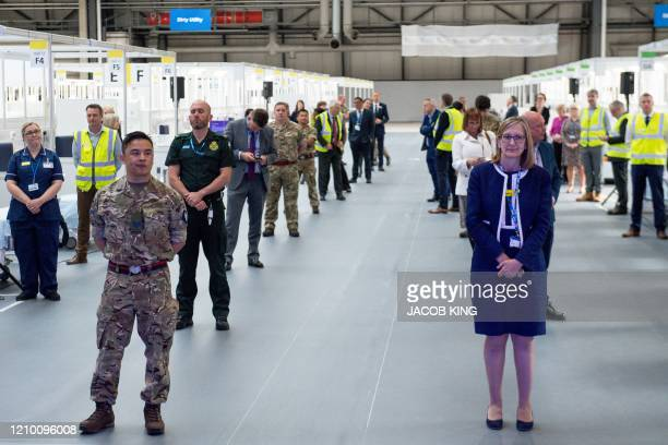 Attendees, including members of the military, health professionals and contactors who helped during the construction, observe social distancing...
